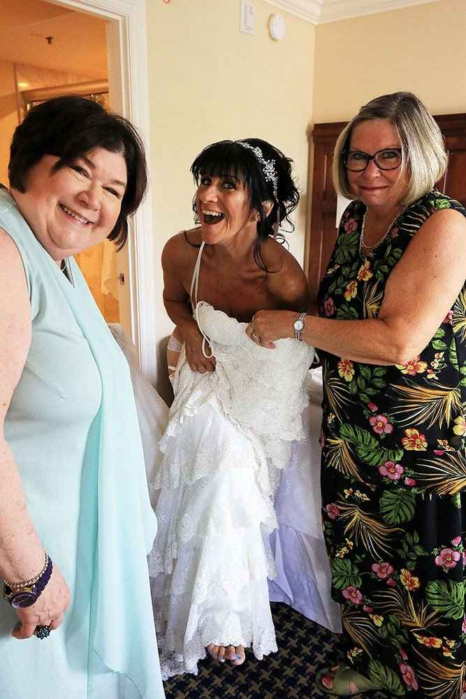 My sisters (who were also my officiant and MOB stand-in) helping me get dressed.