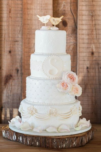 intricate detail wedding cake with roses and bird cake topper