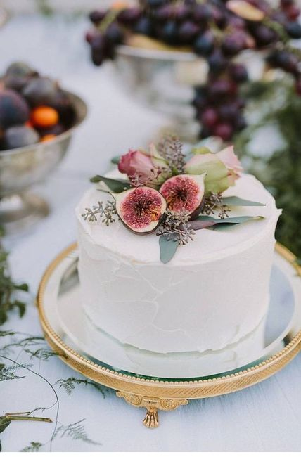 small wedding cake on stand with fruit
