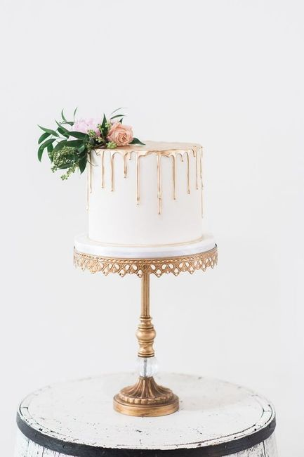 small wedding cake on tall stand with gold detail