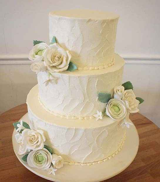 white round wedding cake with roses and greenery