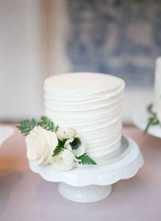 small wedding cake on stand with flowers