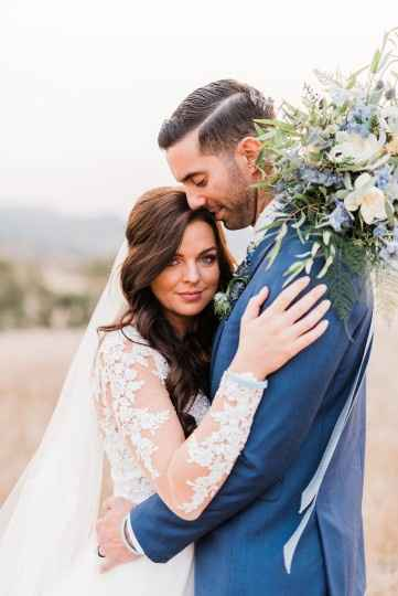 couple holding each other with blue bouquet in field by Brittany Taylor Photography in CA