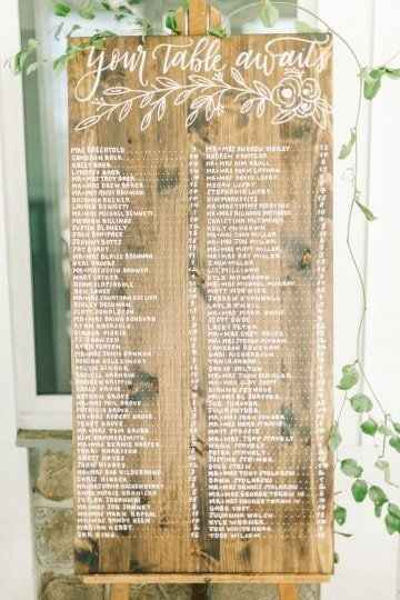 wooden guest list sign with greenery and script writing