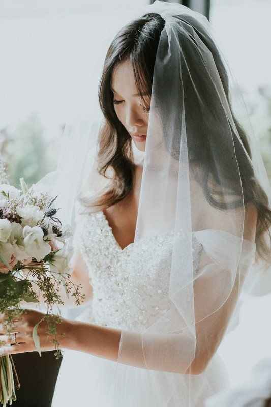 bride with vneck dress holding a bouquet wearing a veil