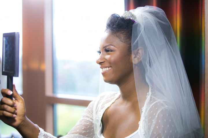 bride wearing a veil looking into mirror
