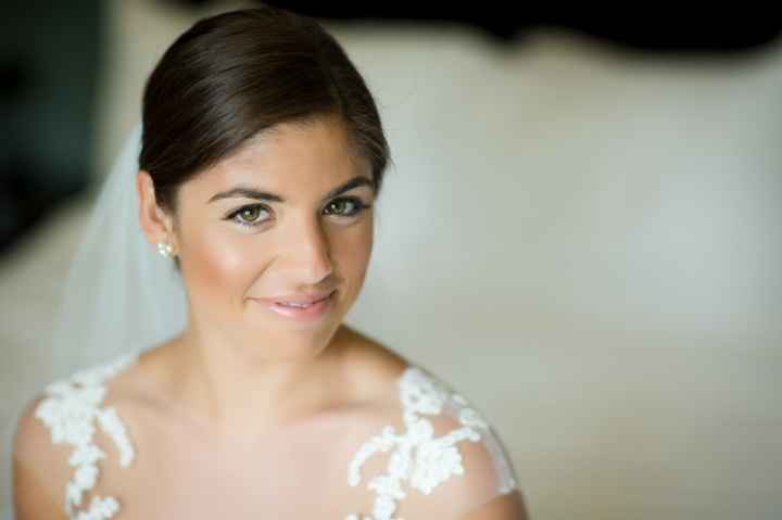 bride wearing a veil smiling in lace dress