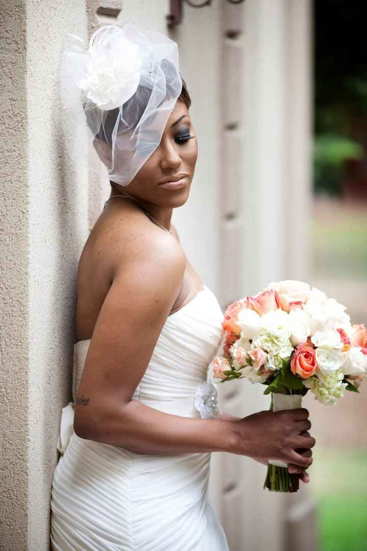 bride wearing a blusher against wall holding a bouquet