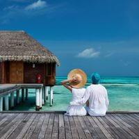 couple sitting on boardwalk in maldives looking at the ocean wearing hats by bungola