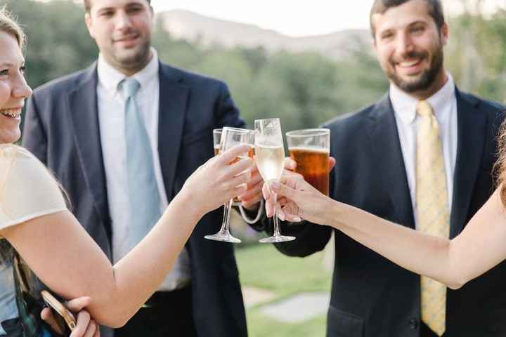 Wedding guests clinking champagne and beer glasses during cocktail hour