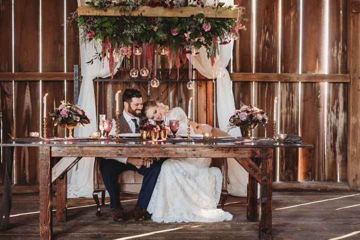 Rustic barn sweetheart table with candles and floral background