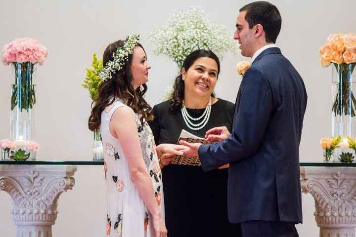 Female wedding officiant marrying couple