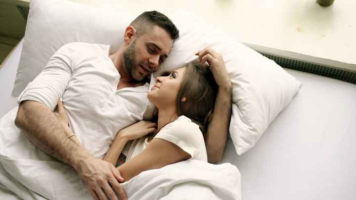 Couple in white talking in bed