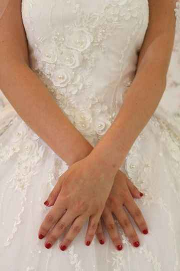 Red nails against wedding dress