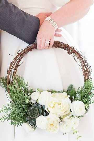 Bride holding branch hoop bouquet with white flowers and succulents