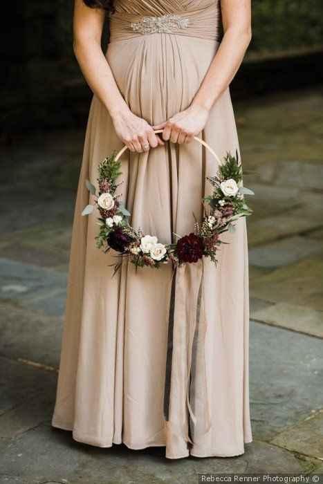 Bridesmaid in tan floor length dress hold hoop bouquet with dark flowers