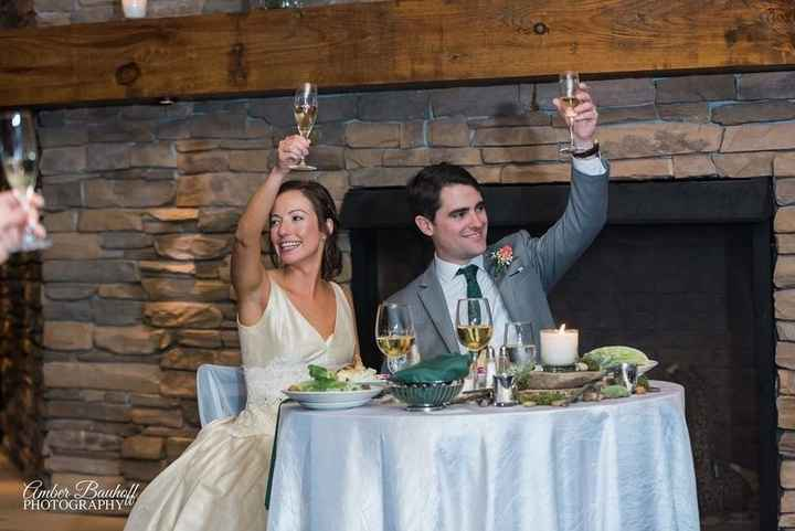 Couple toasts with champagne glasses at sweetheart table