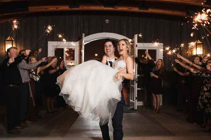 Couple makes grand sparkler exit with the groom carrying the bride in his arms
