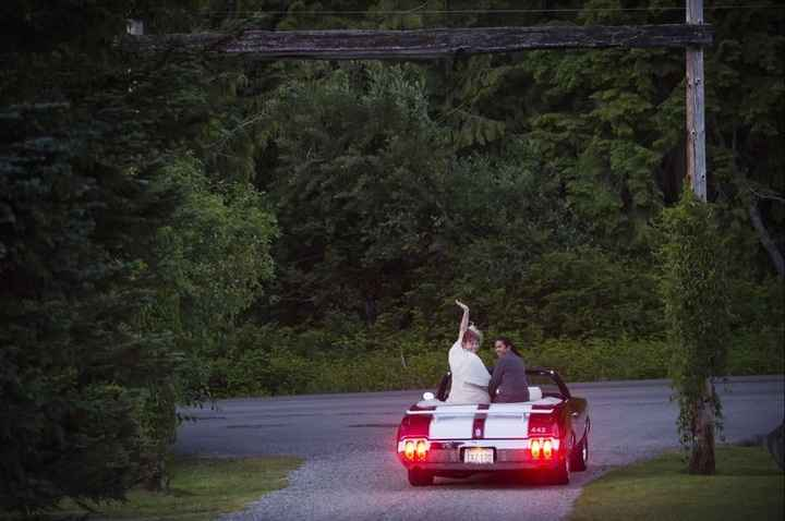 Recently married couple drives of in black convertible with two white racing stripes
