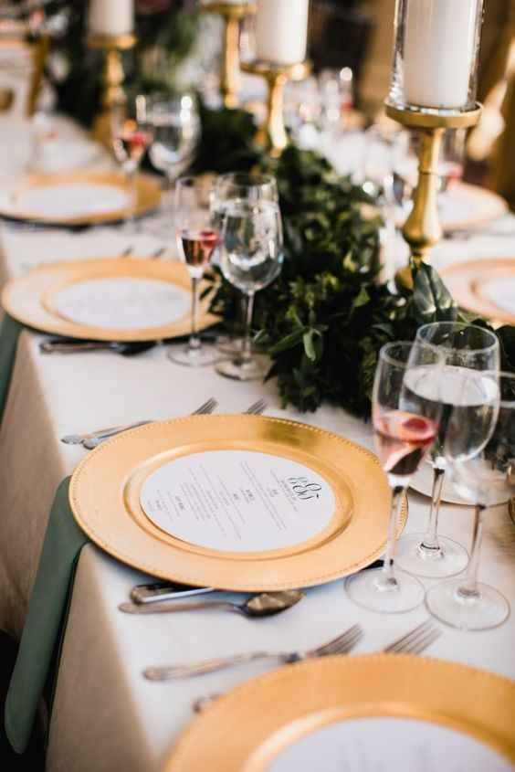 Circular menus on top of gold chargers with set table