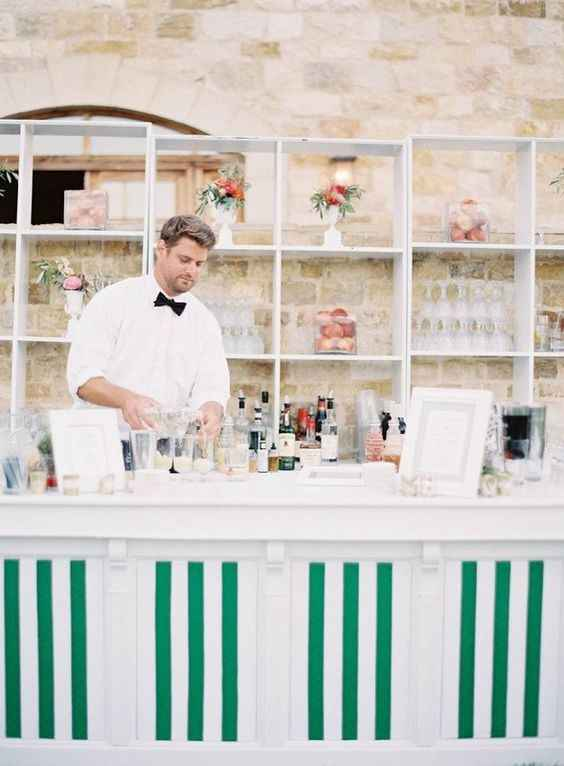 Green and white cocktail bar with bartender