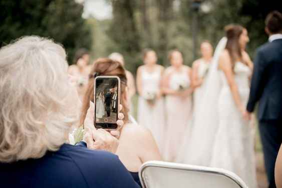 Stock photo of guest taking a picture at wedding ceremony