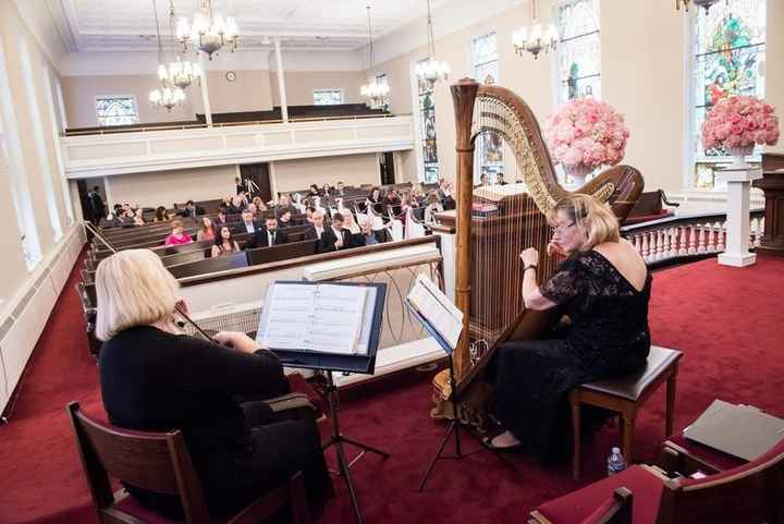 Violinist and harpist play at church wedding ceremony
