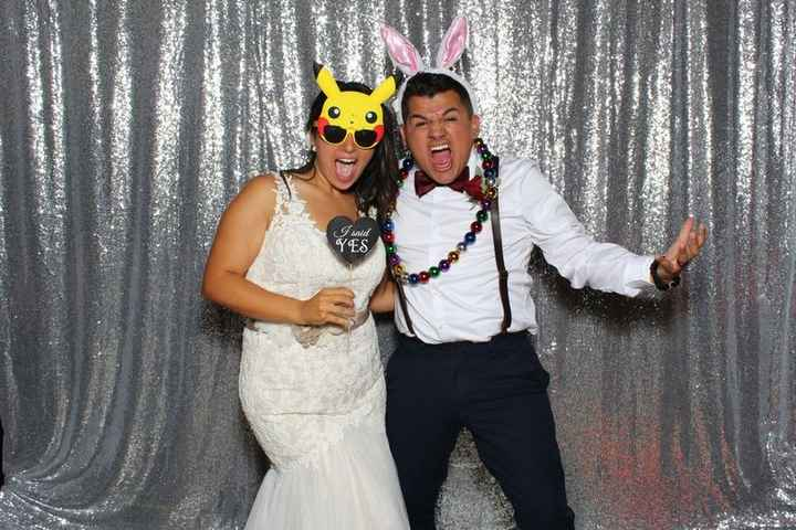 Newlywed couple in photo booth with fun accessories