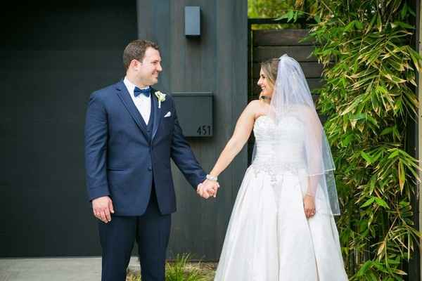 Groom in navy tux and bride in white gown and veil holding hands
