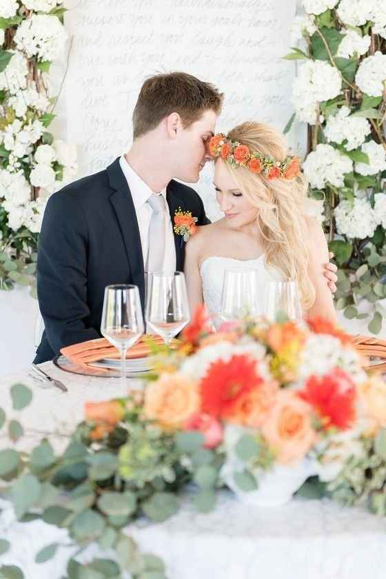Couple at sweetheart table with bright orange and pastel flowers