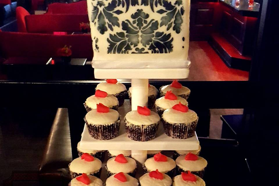 6in Square Damask Cake and 6 Dozen Cupcakes for a Wedding.  Cake and cupcakes both Red Velvet with cream cheese-buttercream frosting. Cupcakes with fondant embossed toppers and a little rose, gumpaste rose cake topper, damask is done is royal icing.
