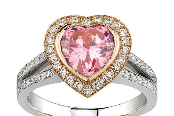 Beautiful Gold and Platinum Engagement Ring with Heart Shaped Pink Diamond with a Gold Halo set with Round Diamonds. Also features a split shank design with channel set Round Diamonds.
