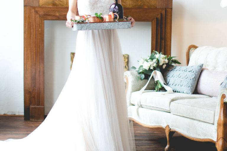 We loved the juxtaposition of soft hues and wood + metal touches for this Georgia wedding styled shoot! Pale pinks graced this inspiration in the form of fabrics – a sweet barely blush wedding gown from Fabulous Frocks of Atlanta, as well as throw pillows and covers for the lounge seating area (with a stunning DIY boxwood wall backdrop).