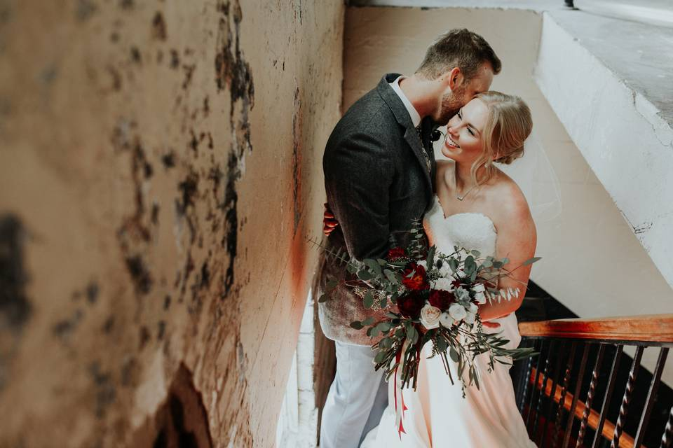 Groom kissing his bride by the stairs