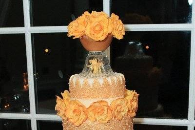 Handmade gold lacework sugar panels drape elegantly over the ivory covered tiers of this 5 tier cake. Covered in over 65 handmade sugar roses.