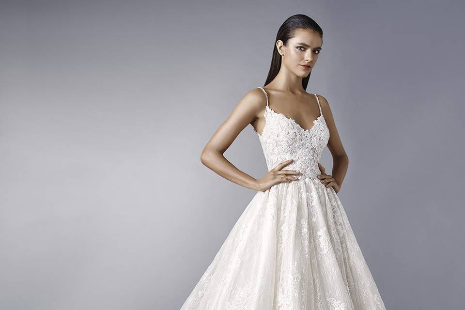 EnzoaniMaddieMake a dramatic entrance with this dreamy ball gown featuring romantic overlace. The V-neckline is supported by rhinestone straps for extra sparkle. Finished with crystal buttons.