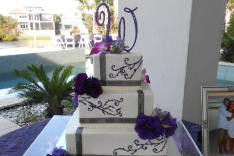 3-tier wedding cake with violet detailing and flowers
