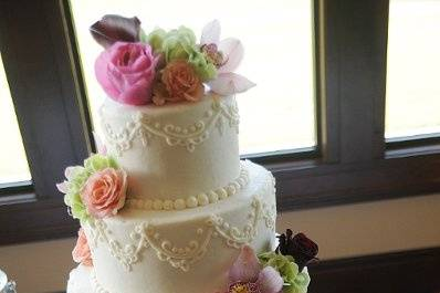 Vanilla/almond cake with almond cream filling.  Ivory buttercream icing with piping and fresh flowers.