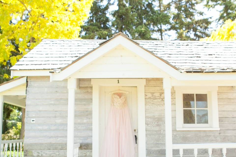 Laura Nichols Photography hangs a bride's dress on our vintage bridal cottage as if to say,