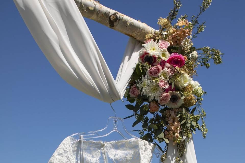 Wedding dress hanging from arbor