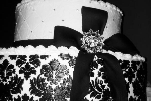 This three tiered butter cream  cake has a black damask pattern and fondant bow with a crystal brooch. LOVELY