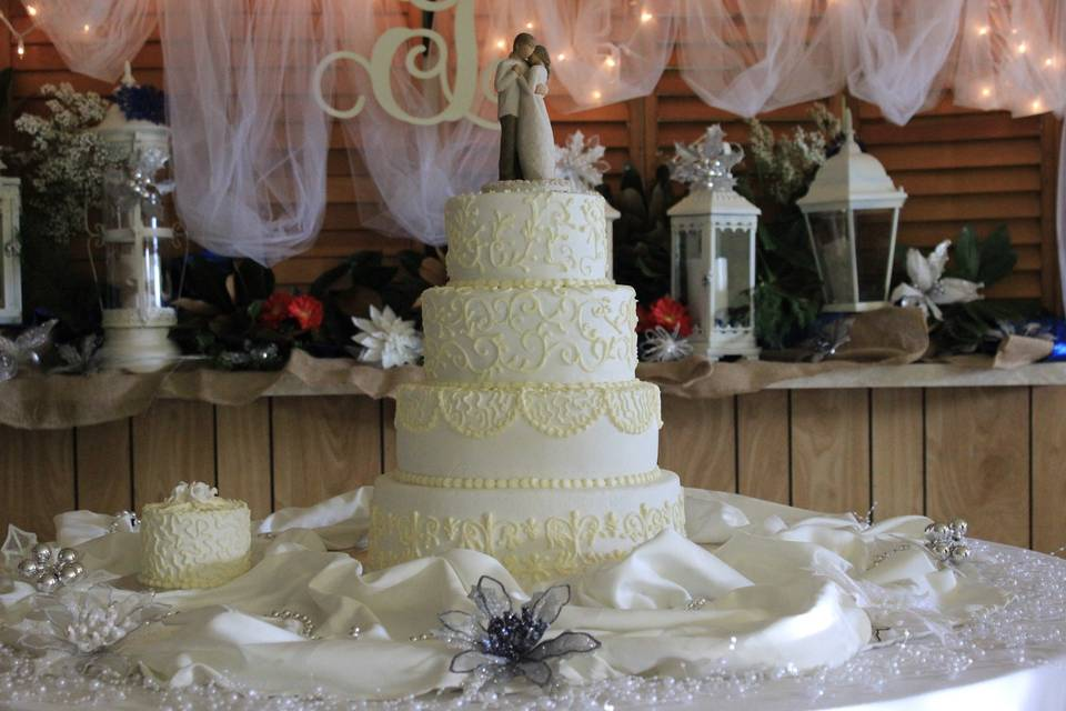Very elegant 4 tier white cake, buttercream icing with the  design in light cream color, with the 1st anniversary on the side