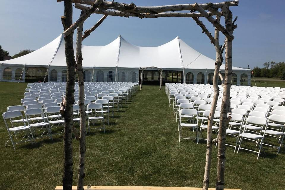White ceremony chairs and tent