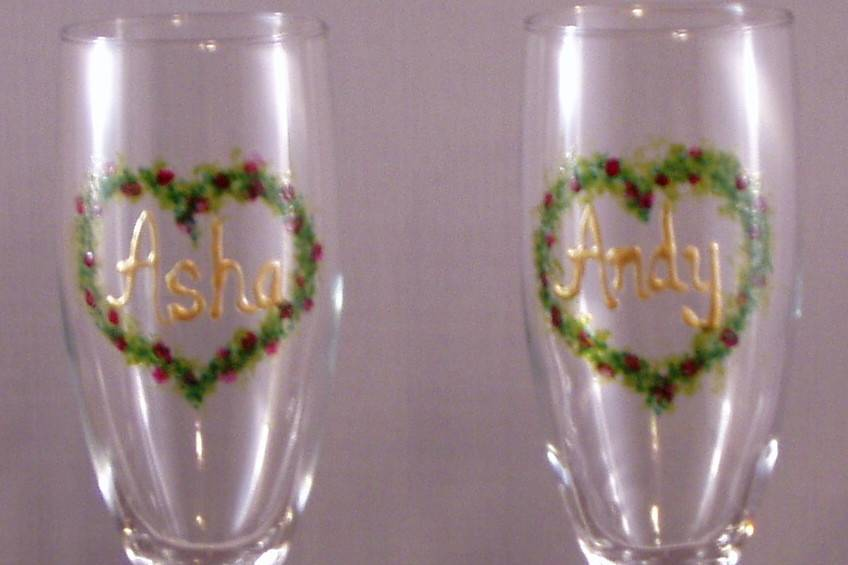 Heartshape garland with flowers in colors that coordinate with wedding colors. Bride and Grooms names on glasses