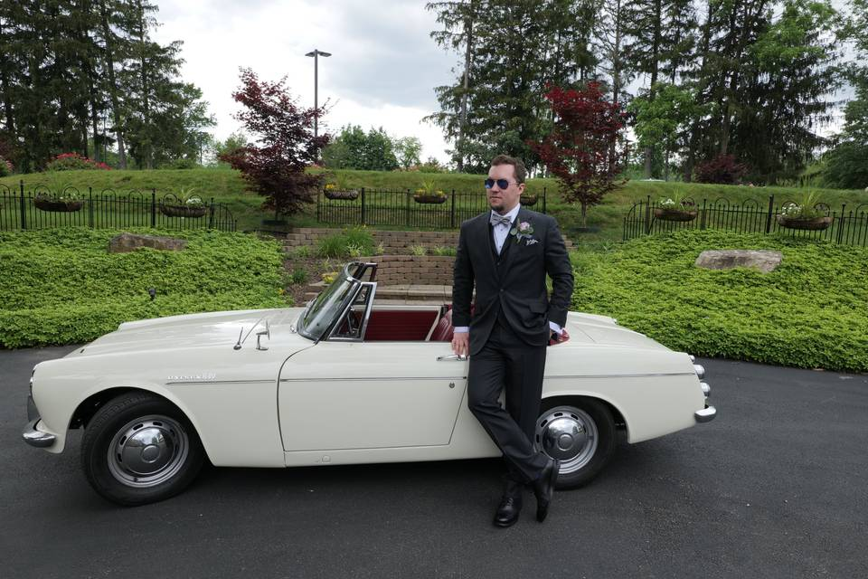 A cool groom with a cool car.