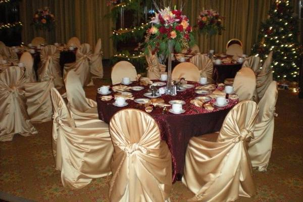 Placesetting with Floor Length Burgandy Cloth and Gold Wrap Around Chair Covers