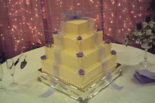 Four tiered pyramid cake with edible roses placed on each corner and a large bow placed as cake topper with the bow ties cascading down on each side. Wedding cake placed on sterling silver plateau.