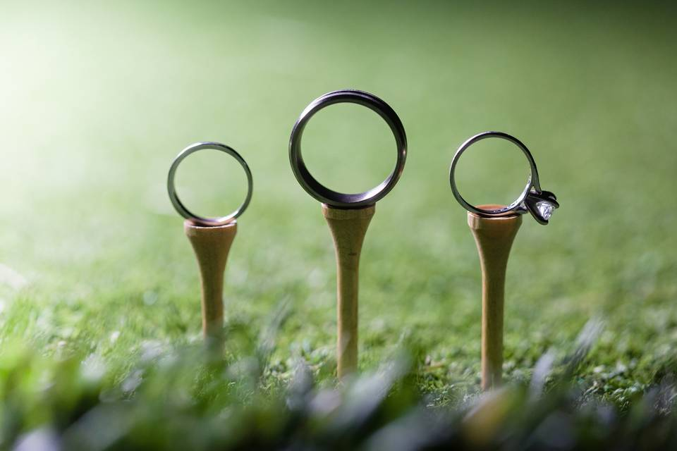 Wedding bands and engagement ring on golf tees
