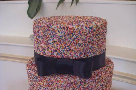 Sprinkled wedding cake with ribbons