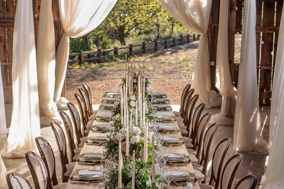 Long table setup with bouquet and candle centerpiece